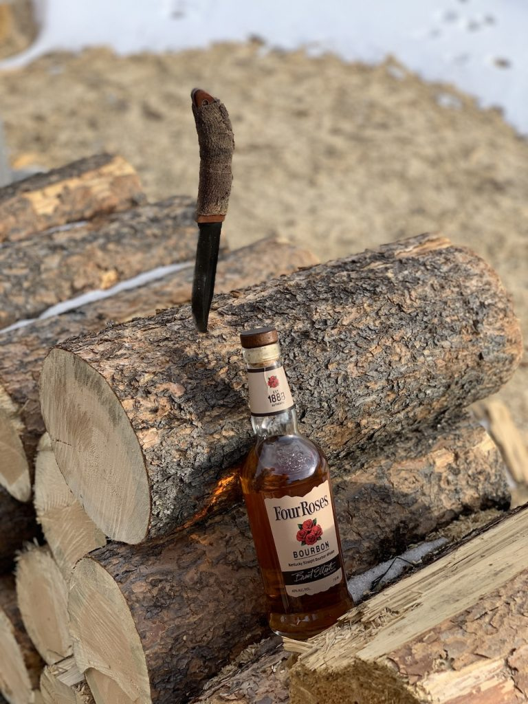 four roses whiskey on a log